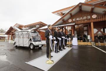自動運転車による運行サービスが始まり、式典でテープカットする関係者=30日午前、秋田県上小阿仁村の道の駅「かみこあに」