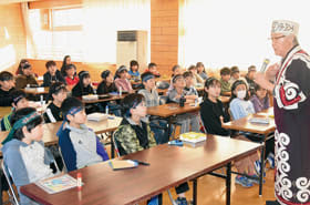 富樫さん(右)からアイヌ民族の文化などについて学ぶ4年生