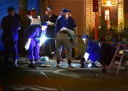 射殺事件があった現場付近を調べる兵庫県警の捜査員=27日夜、尼崎市神田南通1