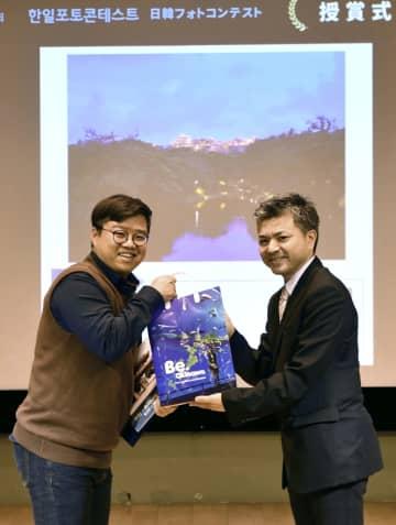「日韓フォトコンテスト」で沖縄県賞を授与される車制ヒョンさん(左)。後方は受賞作品=30日、ソウル(共同)