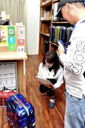 男性から預かったスーツケースを撮影する店員=神戸市中央区北長狭通1
