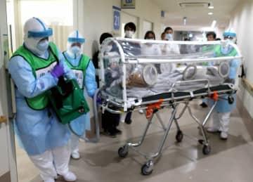 ビニールの覆いがついたストレッチャーで、患者役の保健所職員を移送する病院関係者(京都府舞鶴市浜・舞鶴共済病院)