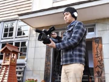 伊参スタジオの前でカメラを構える赤羽さん