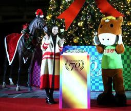 点灯したクリスマスツリーの前で、阪神競馬場開設70周年を祝う相武紗季さん=30日午後、宝塚市駒の町(撮影・風斗雅博)