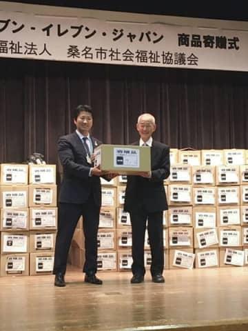 【商品寄贈式で商品が入った段ボールを受け取る山中会長(右)=桑名市総合福祉会館で】
