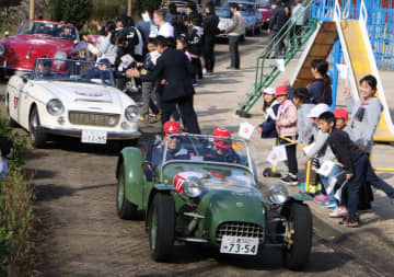 学校を訪問したクラシックカーを見送る児童ら=平戸市立根獅子小