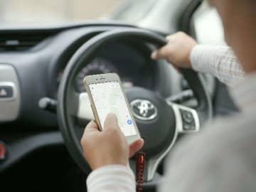 スマホなどを操作しながら車を運転する「ながら運転」が12月1日から厳罰化される(写真はイメージ。実際には運転していません)