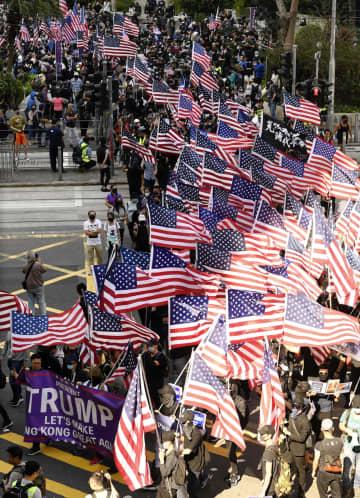 米国で成立した「香港人権・民主主義法」を歓迎し、デモ行進する市民ら=1日、香港(共同)