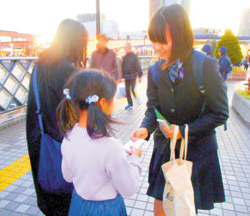 通行人に啓発品を手渡す女子高校生(右)=JR川口駅(同署提供)