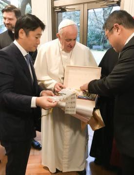 橋本正裕町長(左)から受け取ったさしま茶のセットを開封するローマ教皇(中央)=都内(境町提供)
