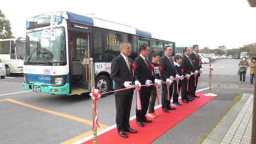 新しいシャトルバスの前で町幹部らが運行開始を祝った=1日、横芝光町