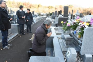 有希ちゃんの墓前で手を合わせる大沢小の福田校長(右)=1日午前、日光市猪倉