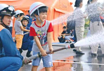 てだこキッズファースト・ファイヤーフェスタで放水体験をする子ども=11月24日、浦添市西洲・サンエー浦添西海岸パルコシティ屋外駐車場