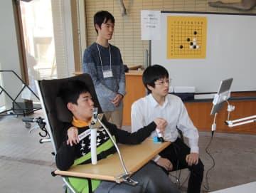 (左から)タブレット端末を操作する東海林さん、大盤解説も行った中川さん、対戦相手の佐野さん。東海林さんは左手のスティックでカーソルを動かし打つ場所を決め、右腕で棒スイッチに触れて確定させた=東京都大田区