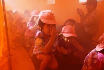 幼年消防クラブ防火研修で煙体験ハウス内を歩く園児ら=11月12日、名護市消防本部