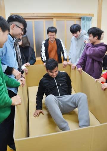 段ボールベッドの強度を確かめる留学生=佐賀市の本庄公民館