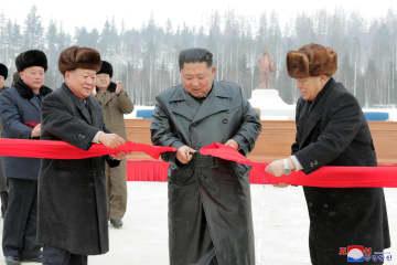 2日、北朝鮮・三池淵邑地区の完工式でテープカットする金正恩朝鮮労働党委員長(中央)(朝鮮中央通信=共同)