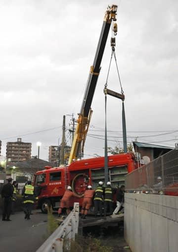 クレーンでつり上げられる消防車=2日午後5時15分ごろ、熊本市中央区坪井4丁目(國崎千晶)