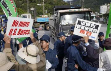 辺野古沿岸部埋め立て用の土砂を積んだトラックに立ちふさがる人たち=3日午前、沖縄県名護市