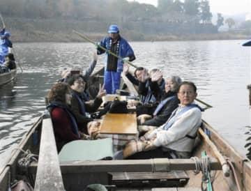 こたつで暖を取りながら川下りに出発する観光客=人吉市