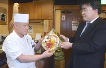 しめ縄を受け取るすし店の原口典人さん(左)=3日午後、札幌市中央区