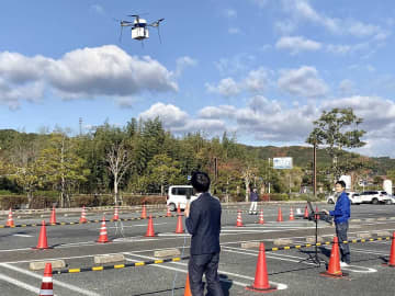 実証実験で食料品を載せて飛び立つドローン=いずれも山口県下関市豊田町、道の駅「蛍街道西ノ市」