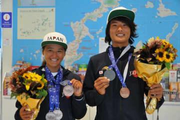 18歳以下で銀メダルを獲得した田口頼さん(右)と2種目で銅メダル獲得した奥秋李果さん=4日、那覇空港