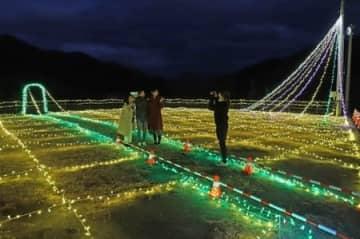 点灯したイルミネーションを背景に記念撮影するリリー&マリーズのメンバー=胎内市下赤谷