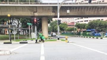 電動キックスケーターの歩道走行は11月に禁止されたが、いまだに歩道を走行する利用者が散見される=4日、シンガポール西部(NNA撮影)