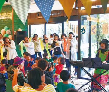 木村真紀さん(右)の伴奏で歌うスイミーのメンバー
