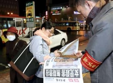 無期懲役の判決を伝える本紙号外を受け取る人たち=4日、新潟市中央区のJR新潟駅前