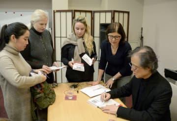 4日、講演後、ロシア語に翻訳された自著にサインする島田荘司さん(右端)=モスクワ(共同)