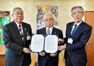 佐藤代表理事(中央)から目録を受ける門馬市長(左)と大和田教育長