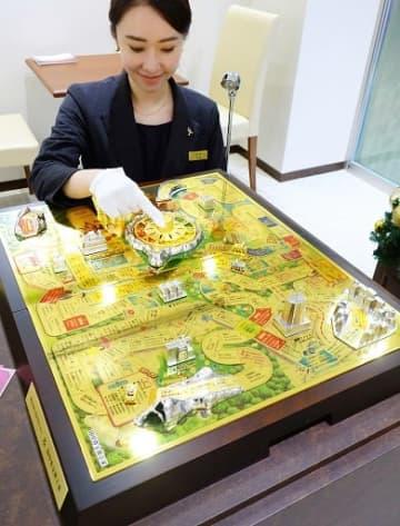 輝きを放つ豪華な「純金製人生ゲーム」=4日、大阪市中央区のギンザタナカ心斎橋店