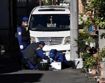 火災のあった住宅地で捜査する千葉県警の警察官=4日、松戸市