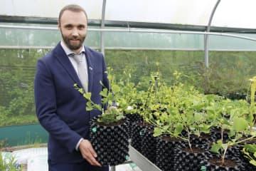 育てたイチョウの苗木を持つウェールズ国立植物園の関係者=6月、英西部ウェールズのラナースニー(共同)
