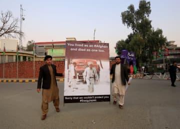 殺害された中村哲さんの肖像を持つ男性ら=4日、アフガニスタン東部ジャララバード(ロイター=共同)