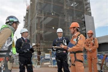 大林組の社員(右)から、説明を受ける熊本労働局の本多信一郎労働基準部長(左から2人目)ら=5日、熊本市西区