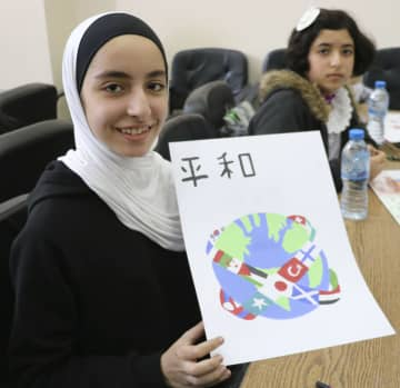 パレスチナ自治区ガザで5日、絵画イベントで平和への思いを込めて絵を描いた子ども(共同)