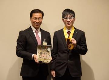 【アビリンピックの電子機器組立種目で金賞を獲得した黒田さん(右)と日沖市長=いなべ市役所で】