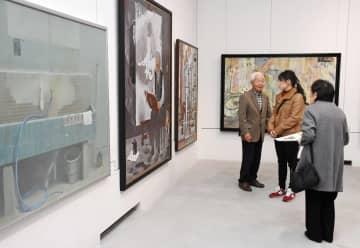 金子剛さん(左)の解説を聞きながら、鑑賞する来場者=佐賀市の県立美術館