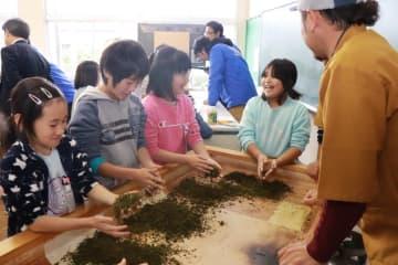 生産者(右)に教わりながら、茶葉の手もみ体験をする児童=彼杵小