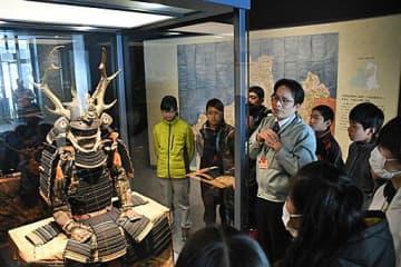 津軽信政が着用した本物の具足について解説を聞く児童