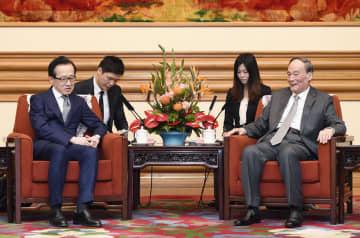 中国の王岐山国家副主席(右)と会談する北村滋国家安全保障局長=6日、北京(共同)