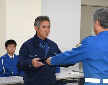 逆走による交通事故を防ぎ、吉田孝夫隊長から感謝状を受け取る岡村三八喜さん(中央)