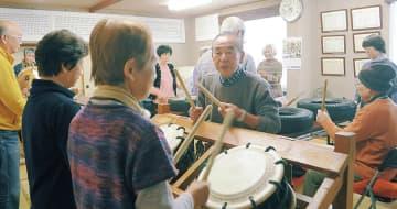 小泉さん(中央)の指導で小太鼓を叩く参加者