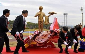 サンジ像を除幕する益城町の西村博則町長(左から2人目)ら=7日午前、町交流情報センター前(後藤仁孝)
