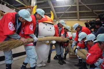 彦根城を飾る迎春用のしめ縄を作る職員とひこにゃん(滋賀県彦根市金亀町)
