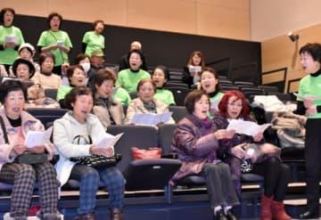 大槌童謡を歌う会のメンバーと合唱し、表情を和ませる参加者