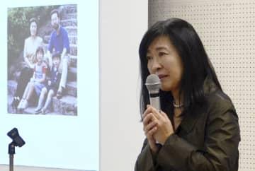 世田谷一家殺害事件の追悼集会で、スクリーンに映された一家の写真を前に講演する遺族の入江杏さん=7日午後、東京都内